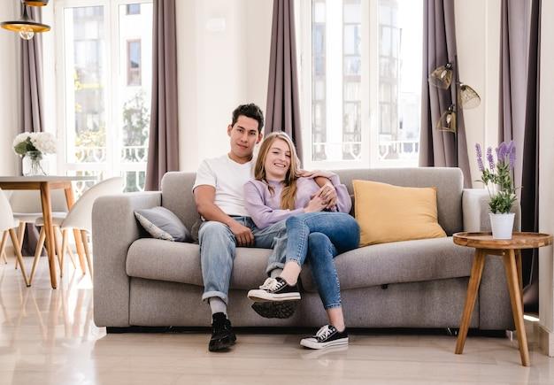 Ritratto di giovane coppia sorridente e godendo insieme seduti sul divano di casa. Foto Premium