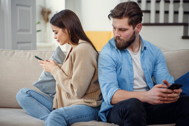 Ritratto di giovani coppie che stanno di nuovo l'un l'altro e che esaminano il telefono.