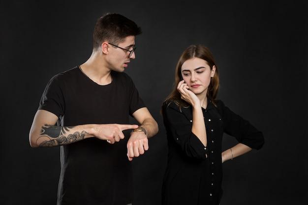 Ritratto di una giovane coppia in piedi con il cellulare, ragazza con cellulare mentre uomo frustrato in piedi vicino isolato su muro nero