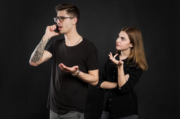 Il ritratto di giovane coppia che sta con il telefono cellulare, uomo sta usando il telefono cellulare mentre la ragazza arrabbiata che sta vicino ha isolato sopra la parete nera