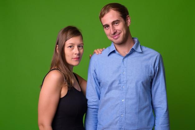 Ritratto di giovane coppia insieme contro il muro verde