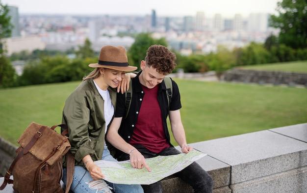 Ritratto di giovane coppia di viaggiatori con mappa in città in vacanza, riposo e pianificazione.