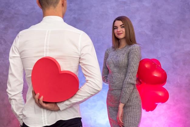 Ritratto di giovane coppia con mongolfiere a forma di cuore rosso. concetto di celebrazione di san valentino
