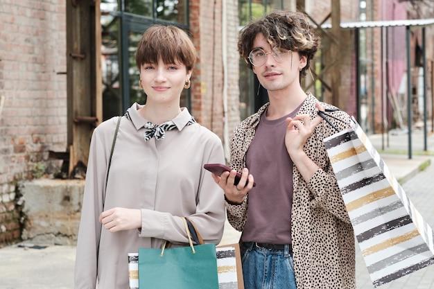 Ritratto di giovane coppia con borse della spesa che guarda l'obbiettivo mentre fanno shopping insieme in città