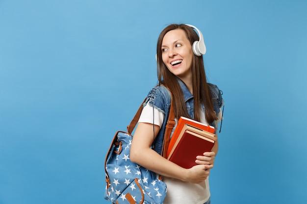 Il ritratto di giovane studentessa curiosa con le cuffie dello zaino che ascolta la musica tiene i libri di scuola che guardano da parte sullo spazio della copia isolato su fondo blu. istruzione al college universitario di scuola superiore.