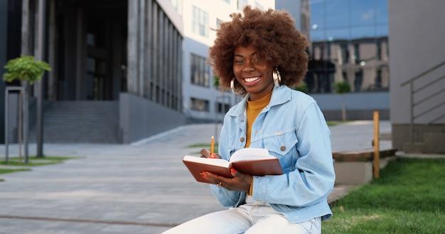 Ritratto di giovane donna afroamericana riccia e carina seduta su una panchina, leggendo un libro di testo, facendo segni e sorridendo alla telecamera.