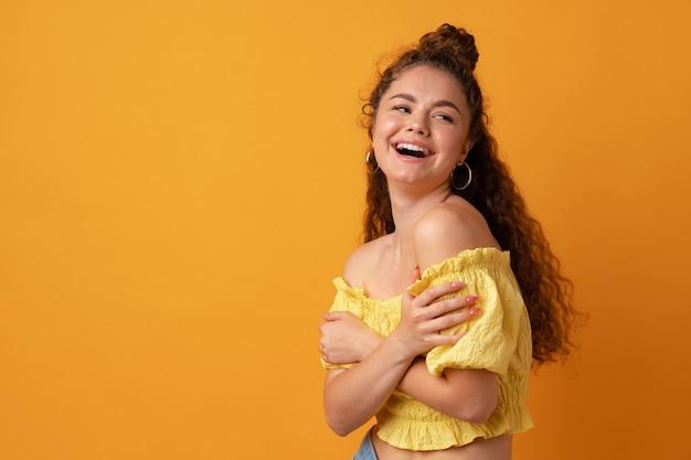 Ritratto di una giovane donna dai capelli ricci su sfondo giallo