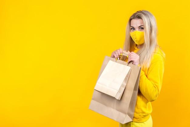 Ritratto di giovane donna bionda carina con eco-bag di carta in maschera protettiva gialla