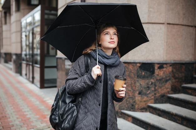 Ritratto di giovane signora carina in piedi sulla strada con ombrellone nero e caffè in mano