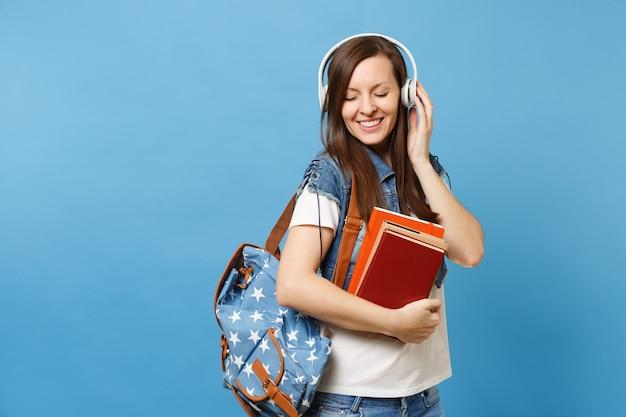 Il ritratto di giovane studentessa rilassata sveglia in vestiti del denim con le cuffie dello zaino ascolta la musica, tiene i libri di scuola isolati su fondo blu. istruzione nel concetto di college universitario di liceo.