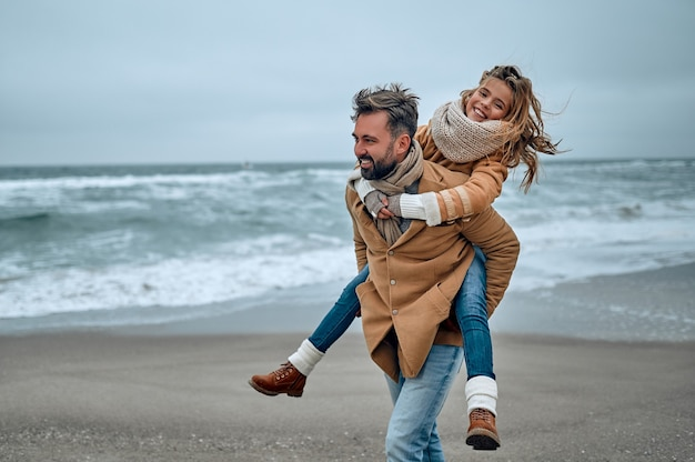 Ritratto di un giovane papà e sua figlia carina che si divertono sulla spiaggia in inverno.