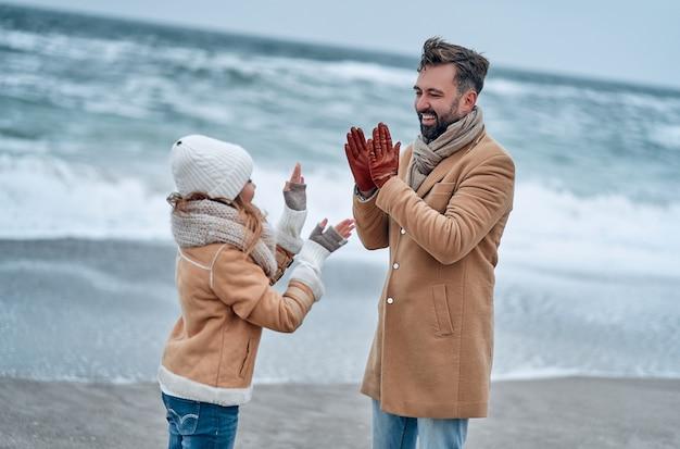 Ritratto di un giovane papà e di sua figlia carina che si divertono sulla spiaggia in inverno.