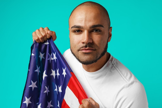 Ritratto di giovane uomo dalla carnagione scura che tiene fiero la bandiera di usa