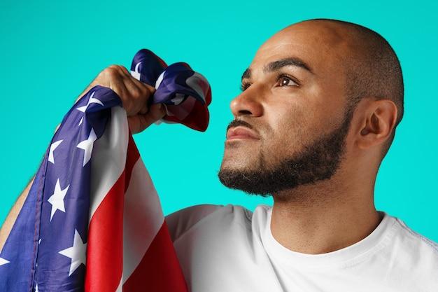 Ritratto di giovane uomo dalla carnagione scura che tiene con orgoglio la bandiera usa