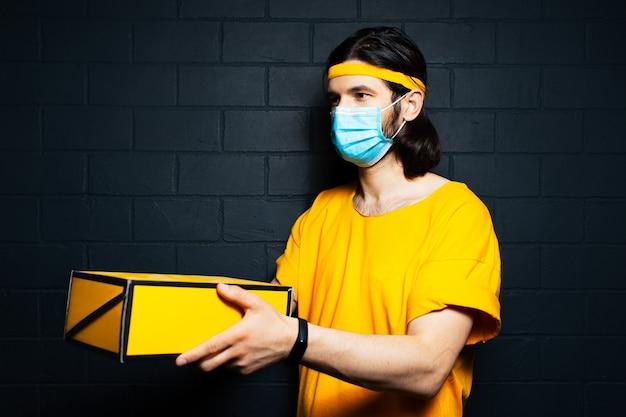 Ritratto di giovane fattorino che dà una scatola gialla, indossa una maschera medica e una camicia arancione sullo sfondo di un muro di mattoni neri. concetto di coronavirus.