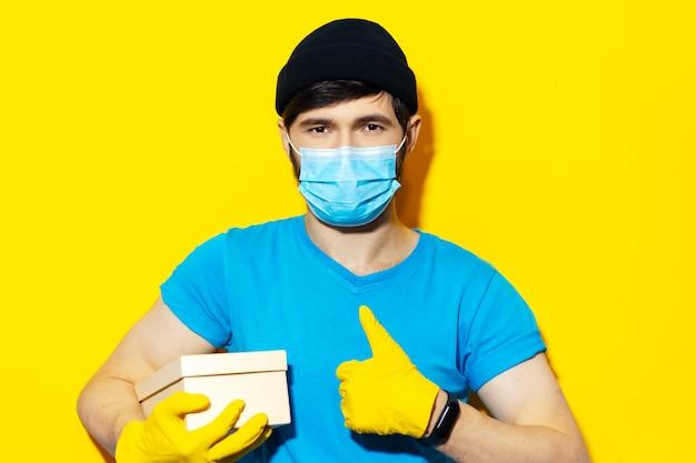 Ritratto di giovane uomo di consegna in camicia blu, indossando maschera medica e guanti gialli