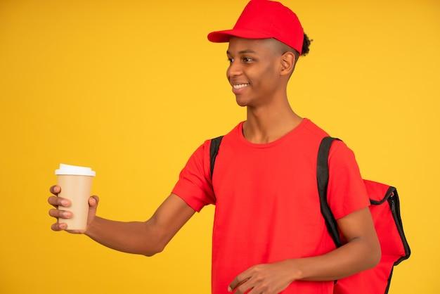 Ritratto di giovane fattorino che tiene una tazza di caffè da asporto. concetto di servizio di consegna.