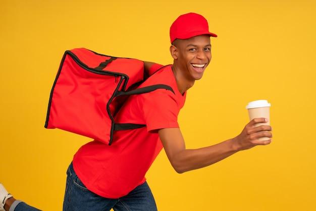 Ritratto di giovane fattorino in uniforme rossa in esecuzione con un caffè da asporto. concetto di servizio di consegna.