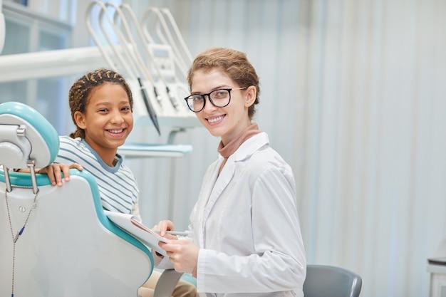 Ritratto di giovane dentista con tessera sanitaria e il suo piccolo paziente sorridente davanti alla clinica odontoiatrica