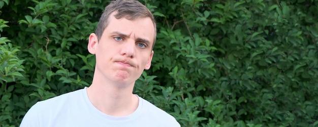 Ritratto di un giovane uomo deluso con gli occhi azzurri su uno sfondo di vegetazione