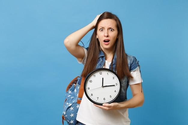 Ritratto di giovane studentessa insoddisfatta con lo zaino aggrappato alla testa, tenendo la sveglia isolata su sfondo blu. il tempo sta finendo. istruzione all'università. copia spazio per la pubblicità.