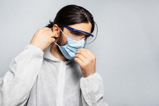 Ritratto di giovane medico che indossa tuta dpi, indossa una maschera medica contro il coronavirus e il covid-19.