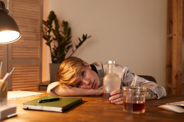 Ritratto di giovane donna ubriaca sdraiato sul tavolo con una bottiglia di whisky vicino a lei che beve alcolici