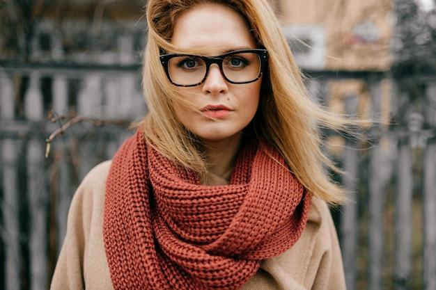 Ritratto di giovane ragazza bionda elegante con occhiali e sciarpa in posa all'aperto