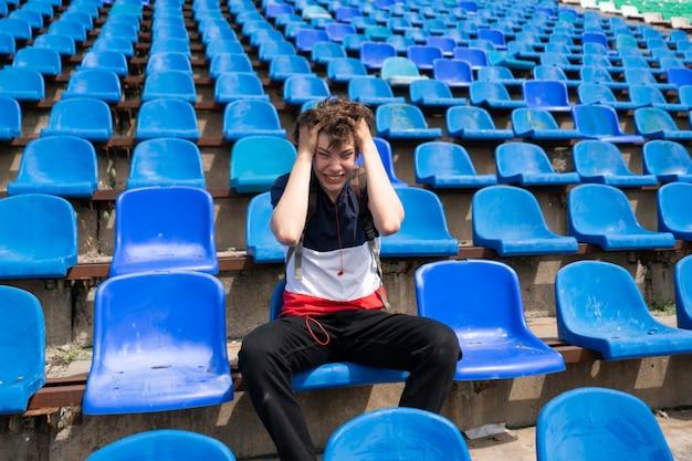 Ritratto di giovane maschio emotivo seduto sullo stadio sportivo durante gli eventi della partita