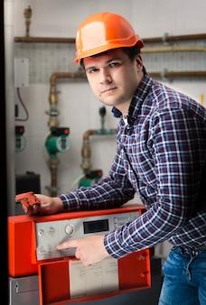 Ritratto di giovane ingegnere che regola il sistema di lavoro sul pannello di controllo