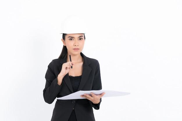 Ritratto giovane donna ingegnere sta presentando idee su piani e progetti, mentre tiene in mano progetti e una penna in studio di ripresa isolato su superficie bianca
