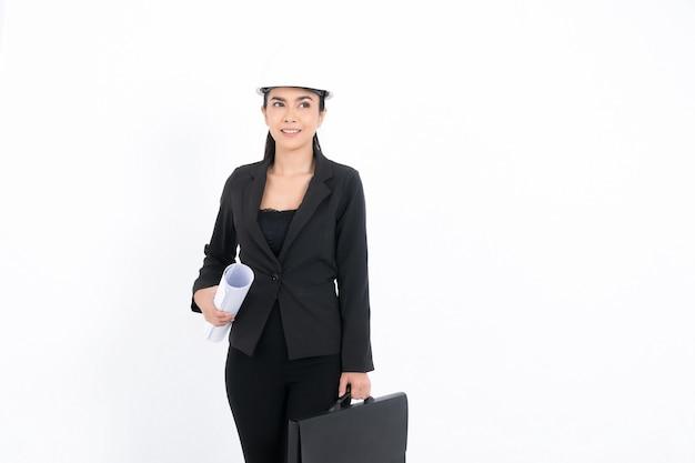 Ritratto di giovane ingegnere donna che indossa abito nero e casco di sicurezza bianco che tiene il progetto e la borsa in studio di ripresa isolato su superficie bianca