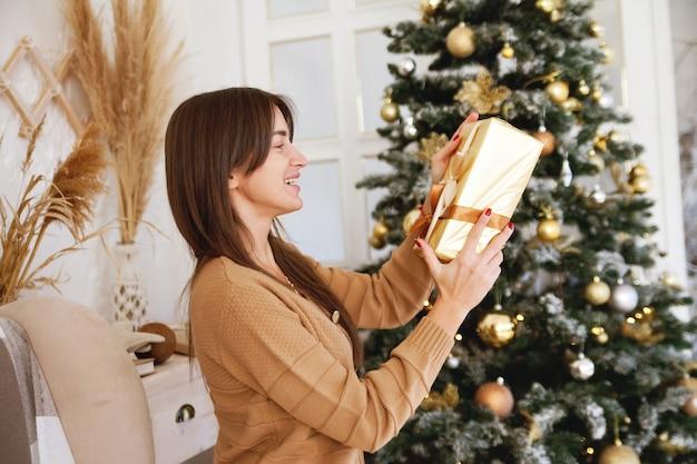 Ritratto di giovane ragazza europea in camera accogliente in stile abbraccio con il regalo di capodanno
