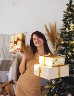 Ritratto di giovane ragazza europea in camera accogliente in stile abbraccio con i regali di capodanno