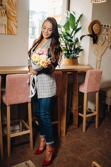 Ritratto di una giovane ragazza europea con i capelli lunghi in un caffè con un bouquet in piedi vicino alla finestra, una ragazza alta in una giacca con i capelli lunghi in un caffè in attesa.