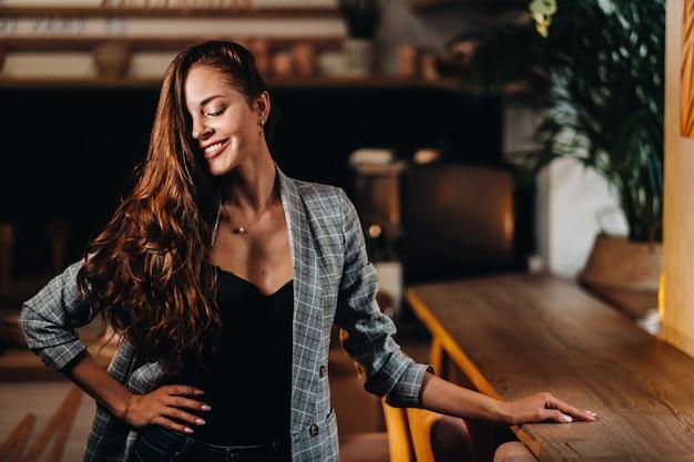 Ritratto di una giovane ragazza europea con i capelli lunghi in un bar nella luce della sera, una ragazza alta in una giacca con i capelli lunghi in un caffè.