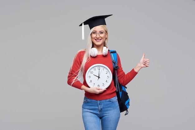 Ritratto di giovane studentessa bionda emozionante in cappuccio laureato con lo zaino che giudica grande sveglia isolata su spazio grigio. istruzione al college. copia spazio per il testo