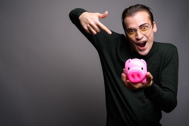 Ritratto di giovane uomo eccitato che tiene banca piggy