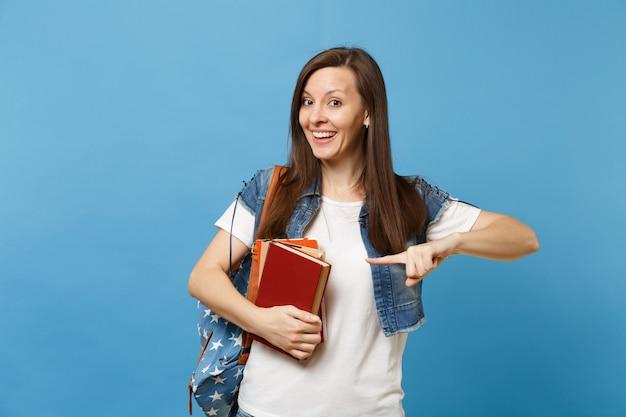 Ritratto di giovane studentessa sorridente emozionante con lo zaino che tiene i libri di scuola che indica il dito indice sullo spazio della copia isolato su fondo blu. istruzione nel concetto di college universitario di liceo.