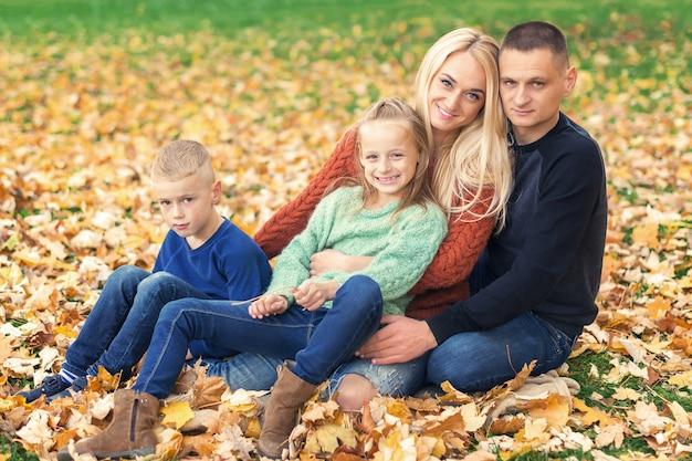 Ritratto di giovane famiglia che si siede in foglie di autunno