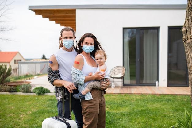 Un ritratto di giovane famiglia con bambino piccolo dopo la vaccinazione covid-9, le vacanze e il concetto di viaggio.