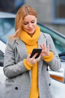 Ritratto di giovane moda bella donna vicino alla sua auto, in città. ragazza dello shopping.