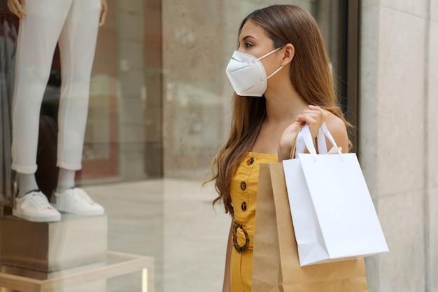 Ritratto di donna moda giovane con maschera protettiva e borse della spesa guardando attraverso la finestra del negozio