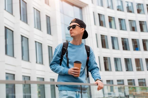 Ritratto giovane uomo alla moda in abiti casual con caffè e occhiali da sole sfondo di un bianco di...