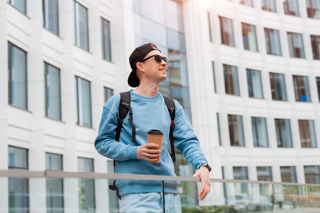 Ritratto di un giovane uomo alla moda in abiti casual con caffè e occhiali da sole e un berretto