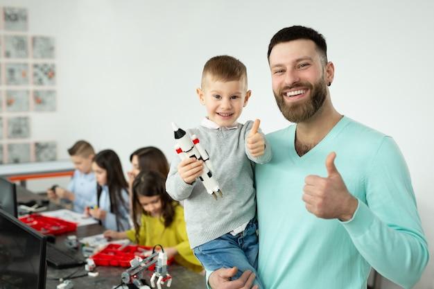 Il ritratto di un giovane padre con suo figlio in braccio mostra i pollici in su in una classe di robotica.