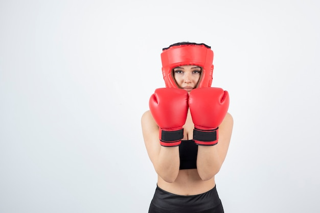Ritratto di giovane pugile femminile in guanti rossi e combattimento casco.