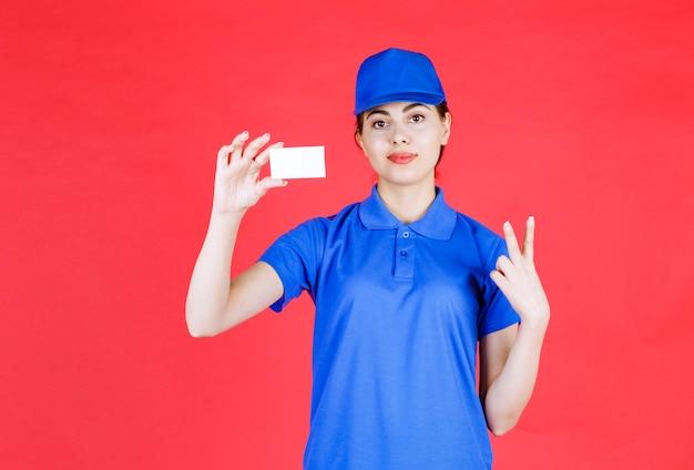 Ritratto di giovane corriere femminile che tiene biglietto da visita vuoto sopra la parete rossa.