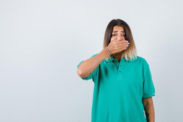 Ritratto di giovane donna che copre la bocca con la mano in una t-shirt e sembra scioccata in vista frontale