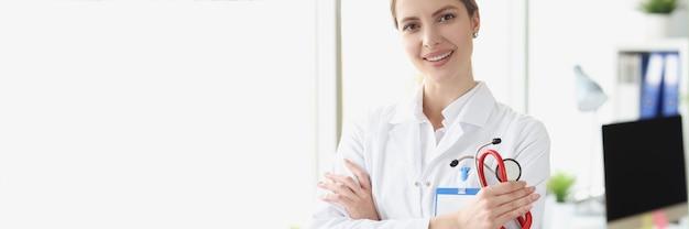 Ritratto di giovane dottoressa in camice bianco che tiene uno stetoscopio nell'ufficio della medina